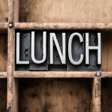"The word ""LUNCH"" written in vintage metal letterpress type in a wooden drawer with dividers."